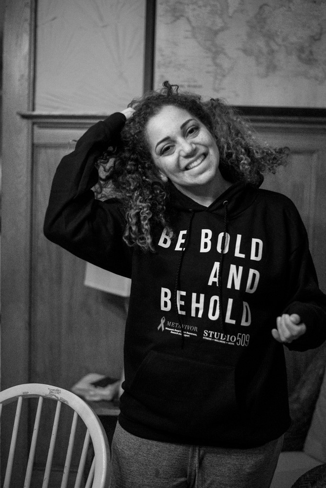 woman wearing be bold and behold sweatshirt, tossing her hair and smiling, metavivor