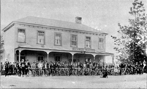 Historic photograp of cyclists gathering outside the Mackaytown Hotel in it's original location