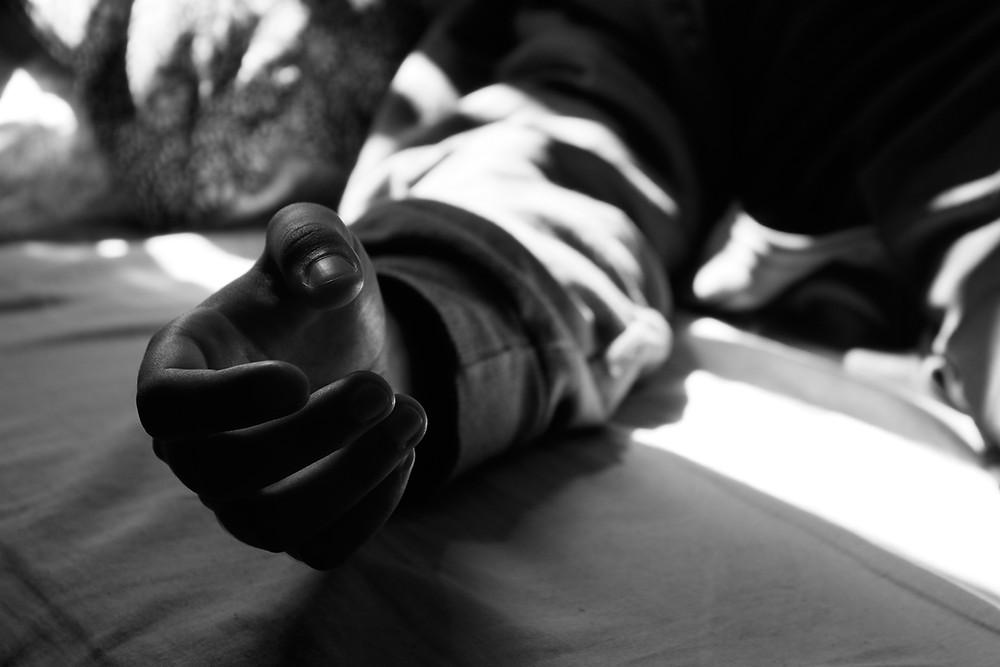Mão deitada na cama, luz de janela, fotografia fine art.