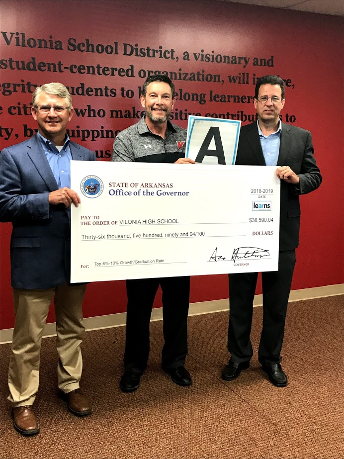 Sen. Hill (left) and Rep. Meeks (right) present a check from the Office of the Governor to Vilonia High School while Dr David Stephens (center), holds Vilonia Middle School's A grade