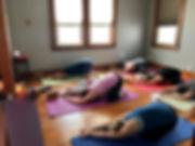 people doing yoga in a studio on yoga mats