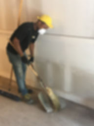team member sweeping debris to complete project
