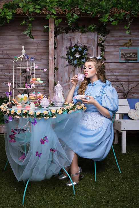 Alice drinking tea sitting at the table.jpg