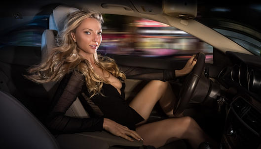 Photo of Sexy blonde woman driving at night