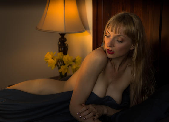 Photo of partially nude beautiful blonde model in bed
