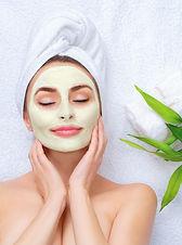 Spa Woman applying Facial clay Mask. Bea