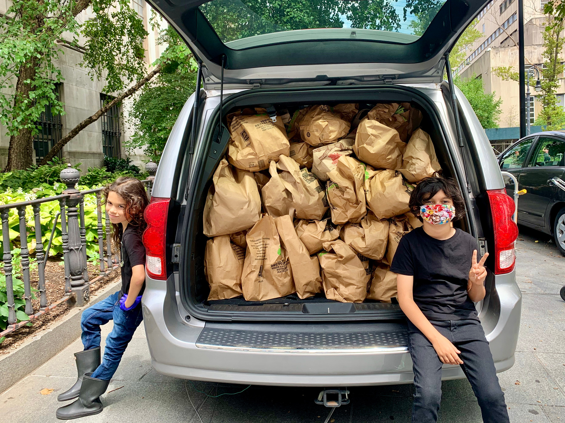 To the left, volunteer Cypress, and to the right, co-founder of Chilis on Wheels, Ollie Carrera in front of a loaded car, on their way to distribution. Kids helping out kids.