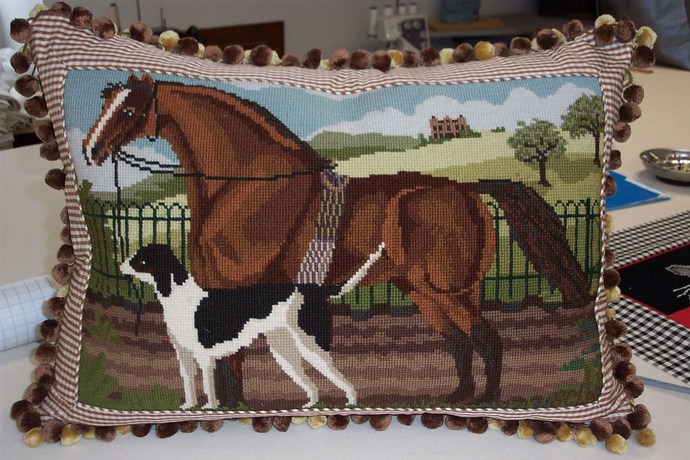 This pillow features an inset needlepoint, fringe and button closure.