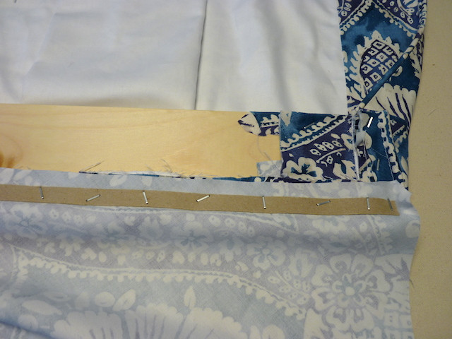 Staple fabric and tack strip to the top of the board.