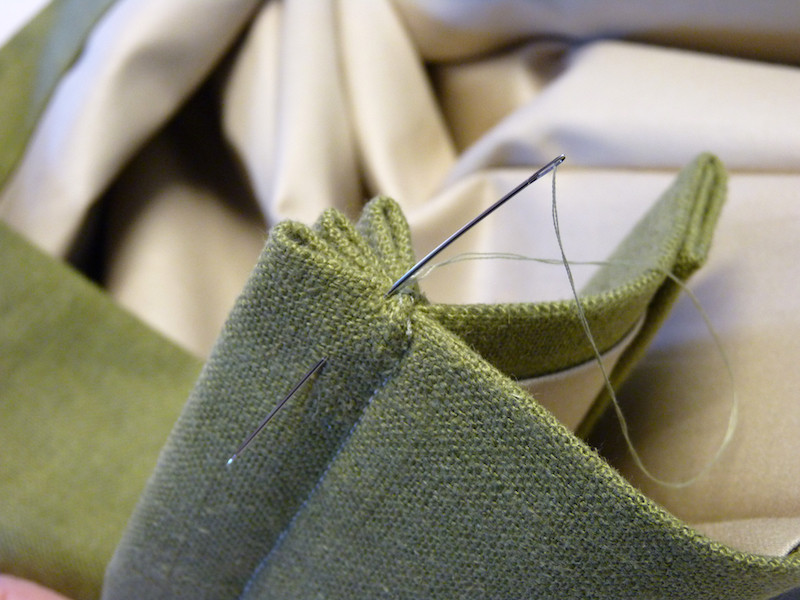 hand sewing a pleated drapery