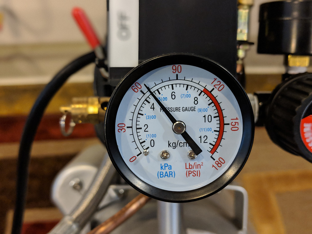 "The pressure gauge on the air compressor shows the ""psi"""