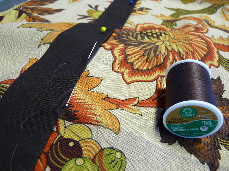 hand sewing banding to the drapery