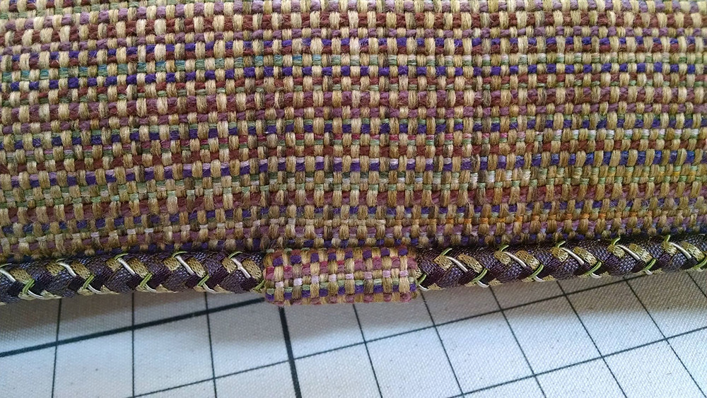Finishing a braided cord by wrapping the join, where the trim butts together with fabric.