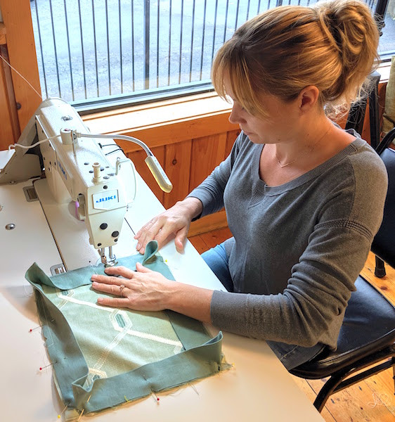 Rebecca sewing a pillow with flanged and mitered corners in class