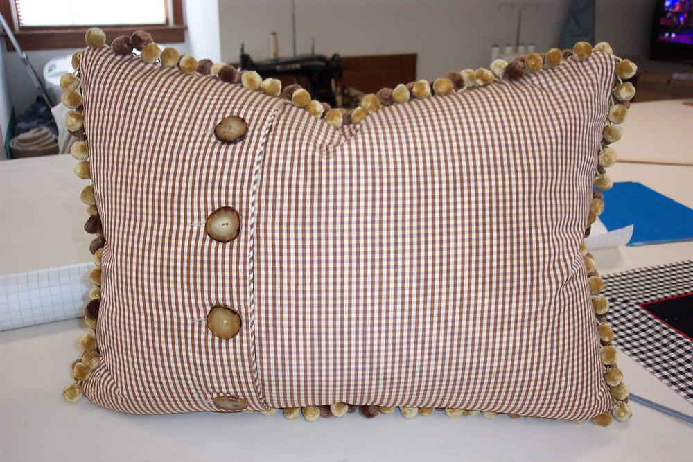 The reverse of this pillow has an off-set button closure.