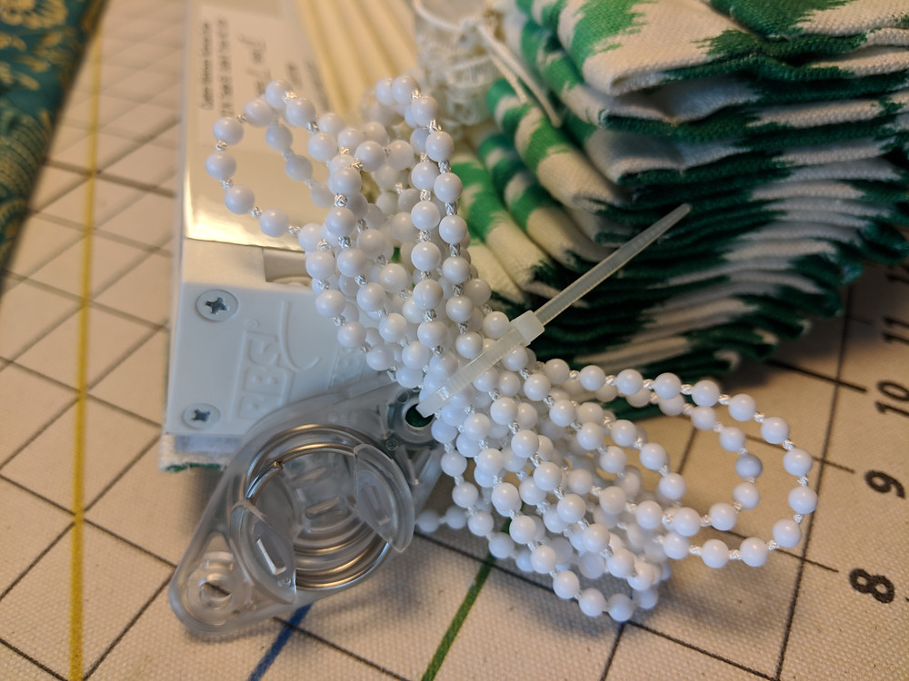 The bead chain loop is secured to the tension device