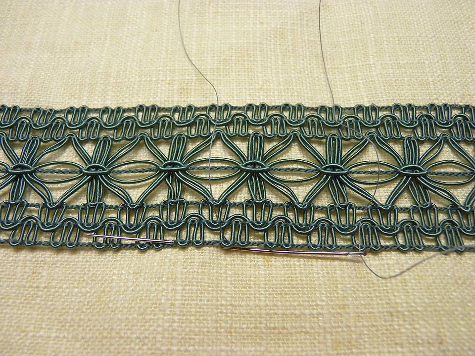 Hand sewing an open weave tape to a drapery.