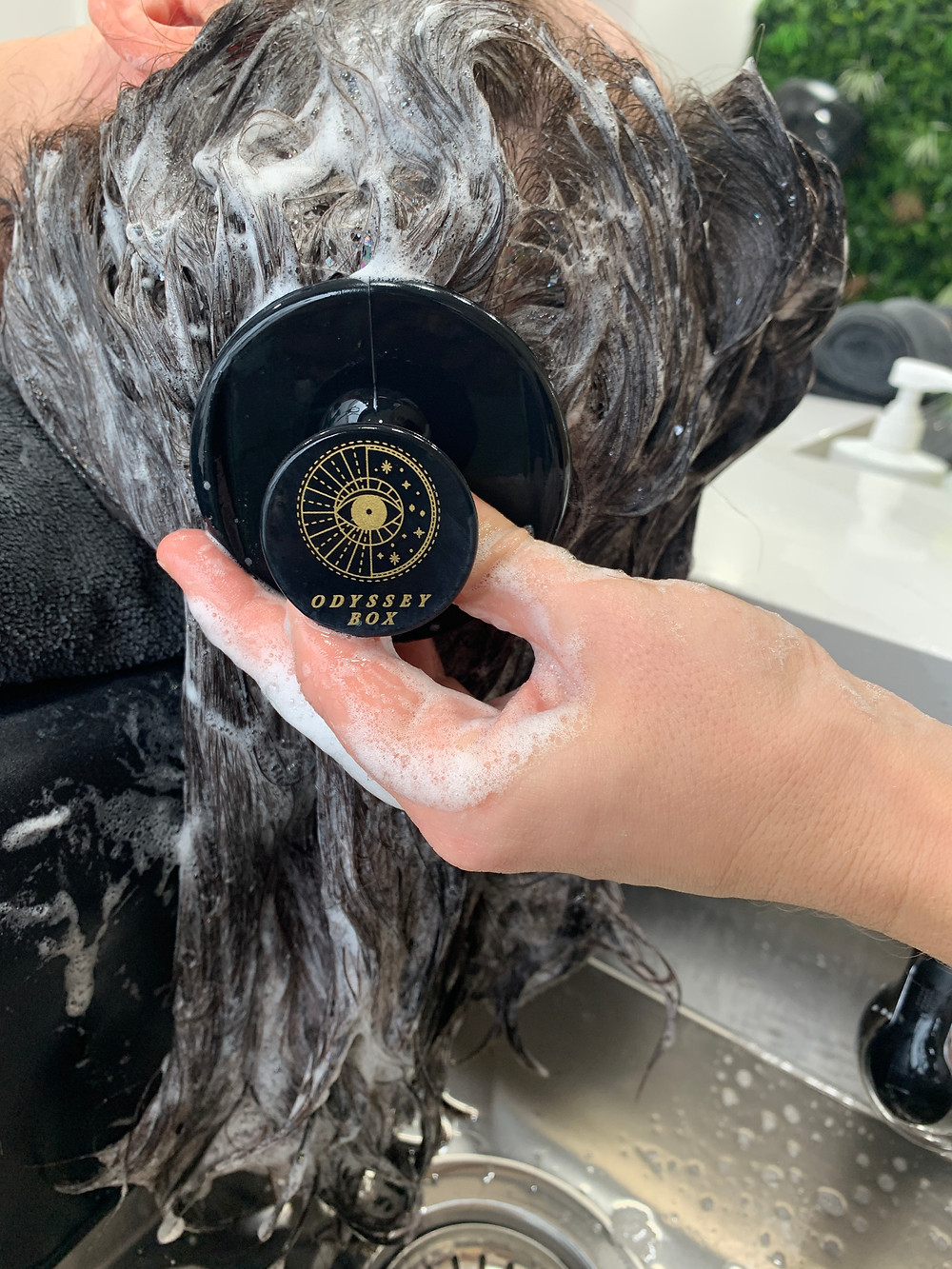 Person with medium length brown hair is having their hair shampooed and scalp scrubbed with an ODYSSEY BOX scalp massager brush
