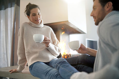 couple-warming-up-by-fire-with-hot-drink