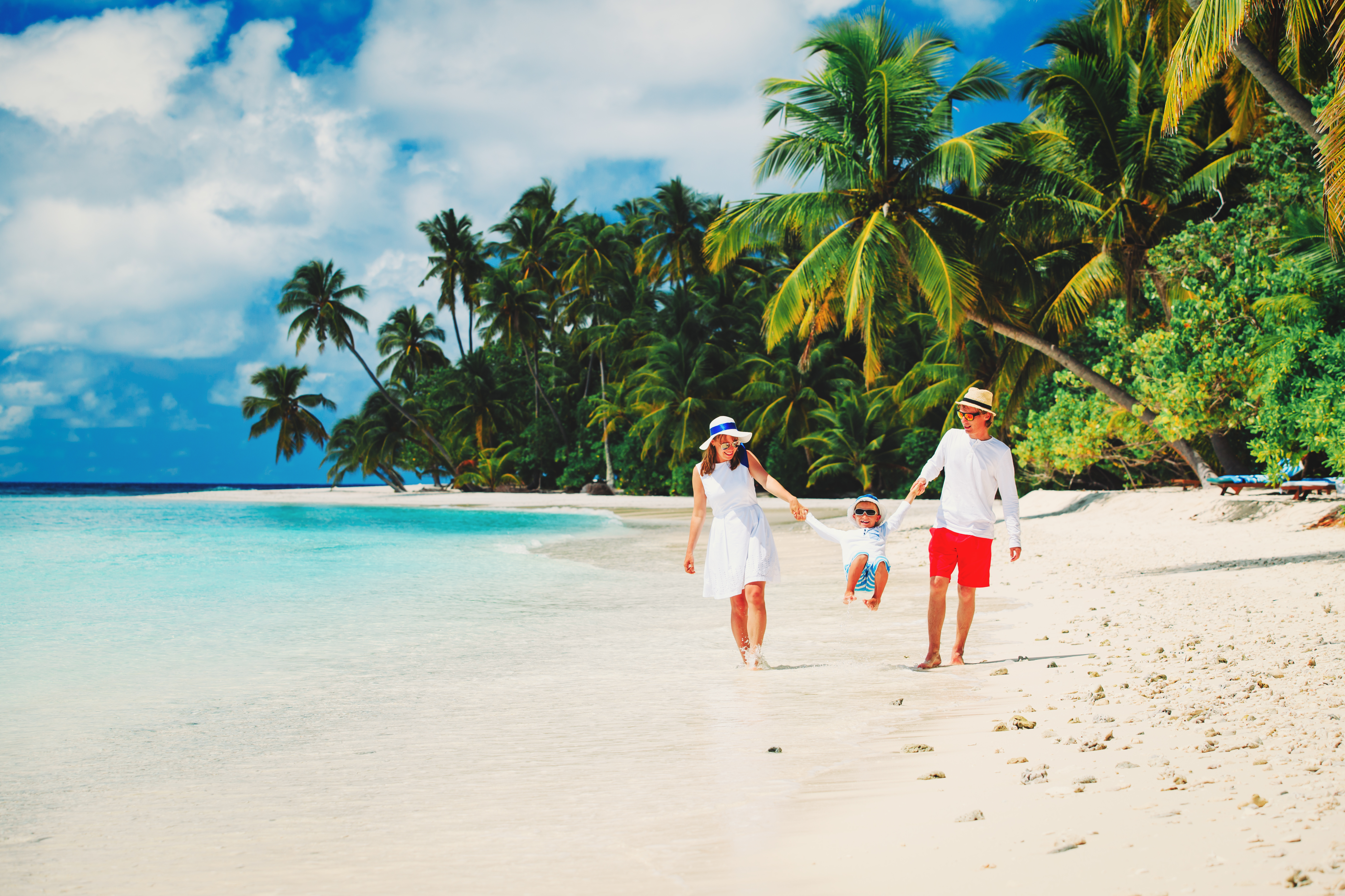 family with kid playing on tropical beac