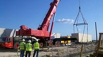 Crane hoisting crated machine tool