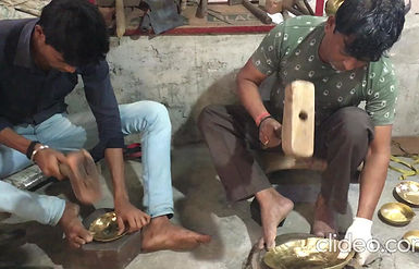 Thatera artisan and apprentice at work making brass bowls