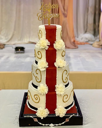 4 tier wedding cake with fresh florals, gold piping, red strip, cake topper