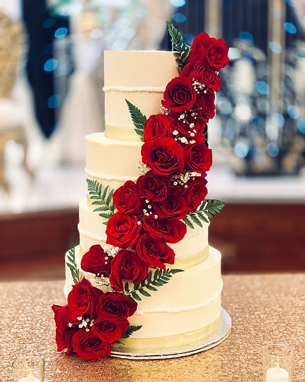 4 tier buttercream wedding cake with a cascade of fresh roses, baby breath, and gold trim