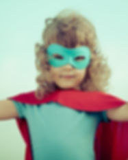 Superhero kid against summer sky backgro