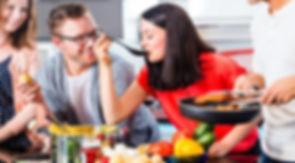 une femme cuisine un bon repas en compagnie de son ami