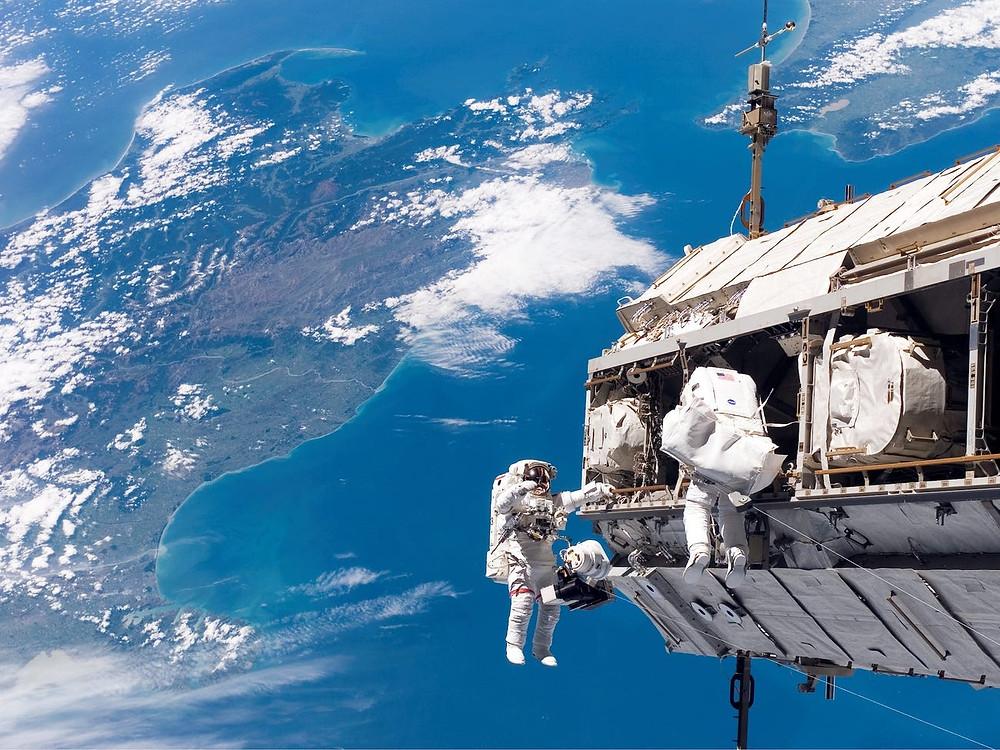 Con el telón de fondo de Nueva Zelanda y el Estrecho de Cook en el Océano Pacífico, los astronautas Robert L. Curbeam Jr. (izquierda) y Christer Fuglesang (derecha) participan en una actividad extravehicular