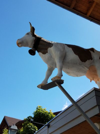 Brown and white cow statue looks down from shop roof onto main street, Adelboden, Switzerland