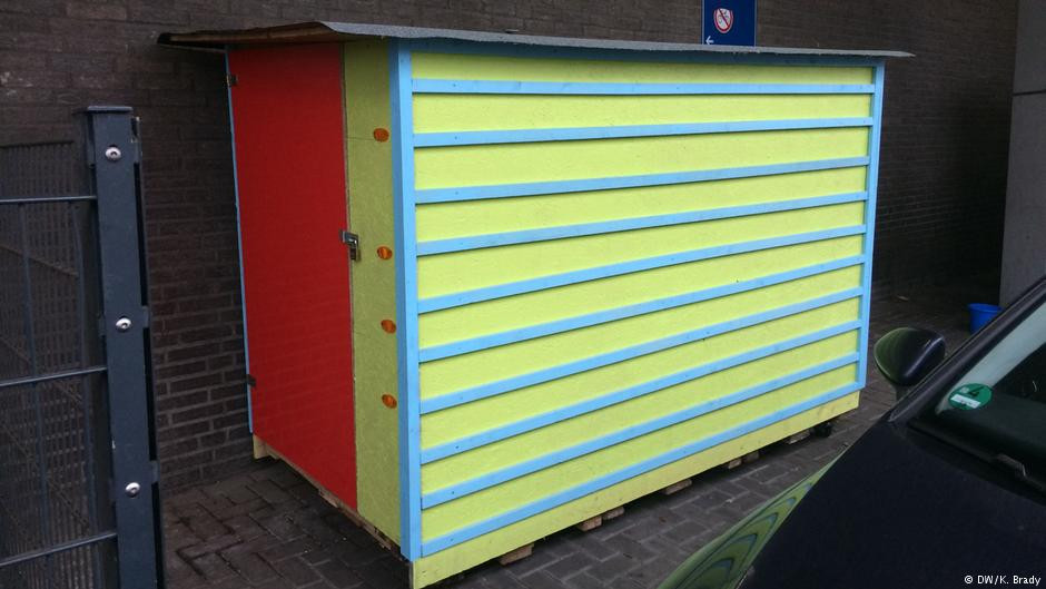 Box in yellow, blue and red, sits on wheels and is lockable home for homeless people.
