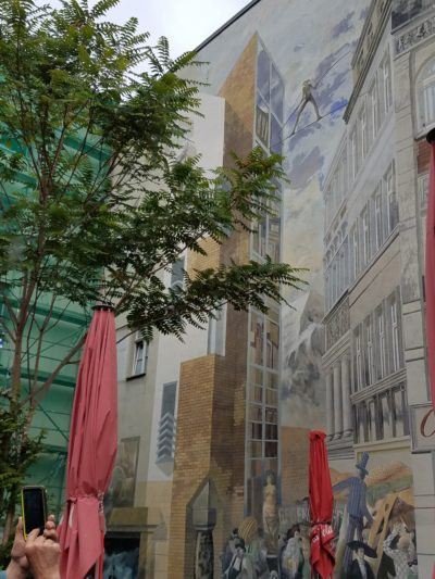 Tromp l'oeil painting of two buildings with tight rope walker between them, audience below.Art on public housing. No graffiti has appeared on this wall. It seems too fun to mess up. Richen