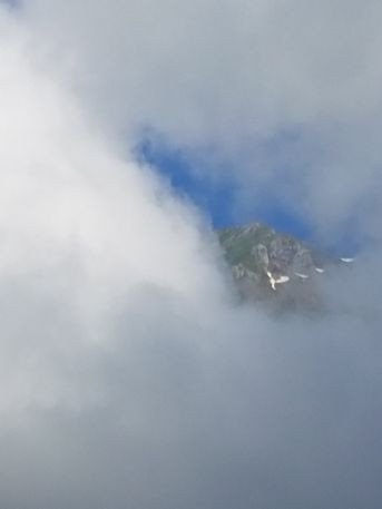 Behind thick clouds, you can barely see the dark rock of a mountain.