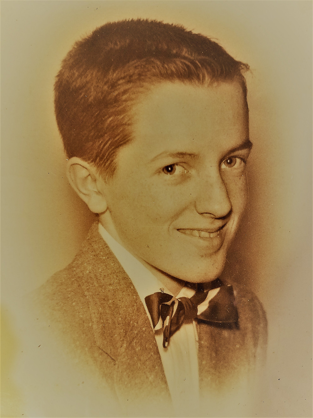 Al at fourteen years, dressed in suit and bow tie for eighth grade graduation. Sepia photo.