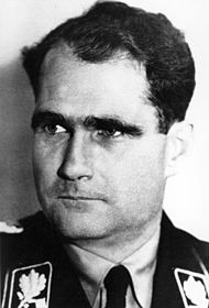 Man in Nazi uniform, dark eyebrows and wavy hair.