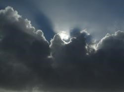 Clouds with sun behind and shinging on the edges, casting dark shadows on the undersides.