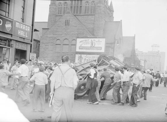 White men turning over a car. Some carrying weapons, 1940s Detroit