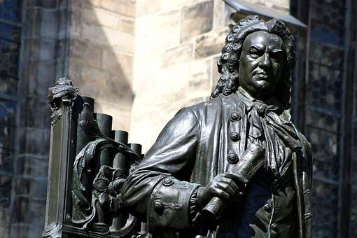 J.S. Bach holding a manuscript and standing in fron of a small organ,in square outside Thomas Kirche Leipzig, Germany