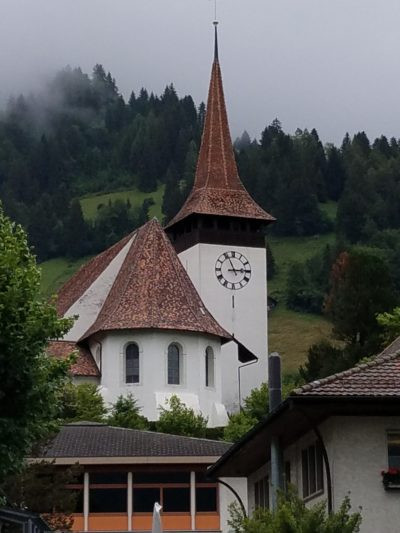The church is white with brown roofing. It's tower sports a clock and a conical cap-like roof.