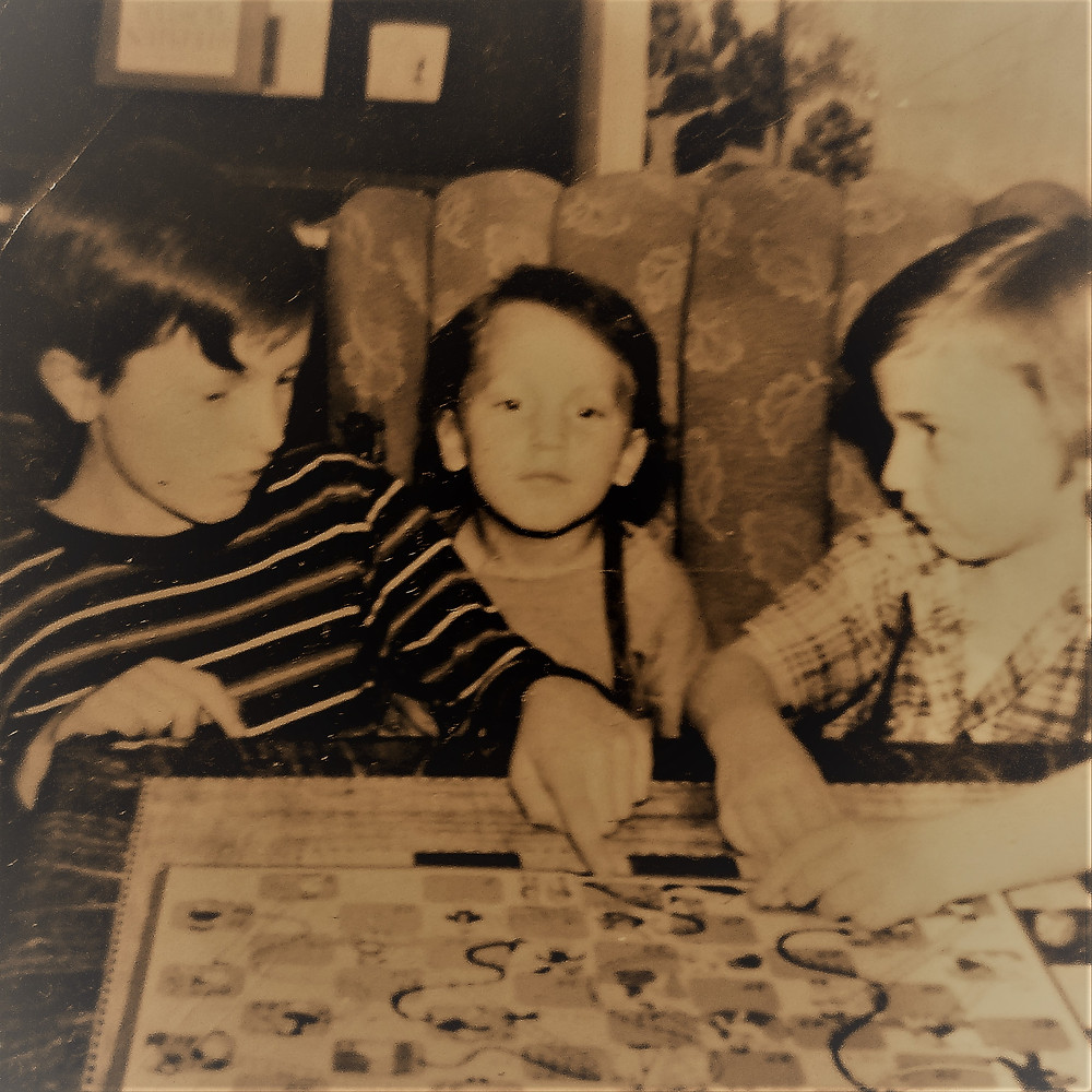 Sepia photo of Al (10 years old) teaching me (5 years) and Jim (3 years) to play Chutes and Ladders. I'm looking miffed that I can't do whatever move I just tried.es