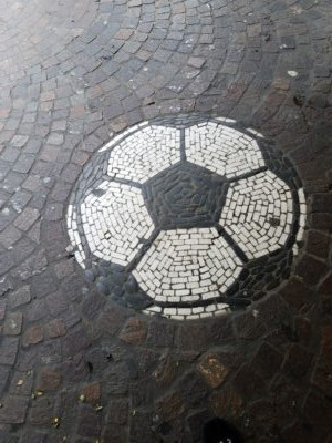 Among the concentric curves of cobblestone, a soccer or futbal sits before the sporting goods stores./Richen