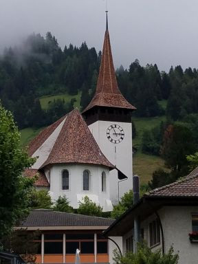 White-walled church and tower sport very steep rooves, very like the pointed hats in many medieval paintings.