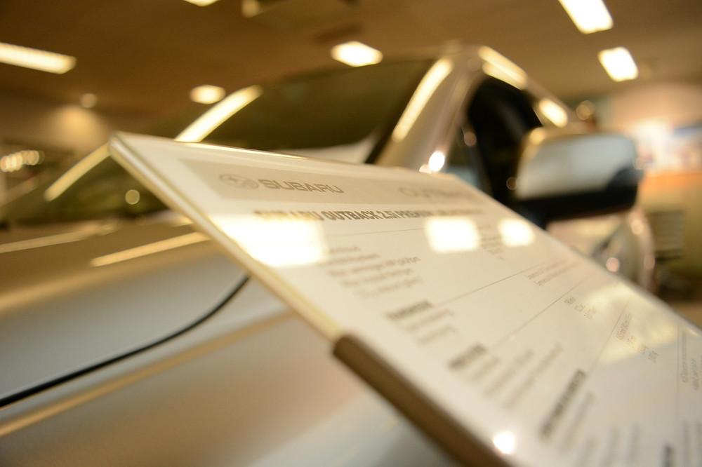 uusi valkoinen auto autokaupassa