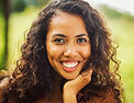 A BIPOC woman with long curly hair smiling.