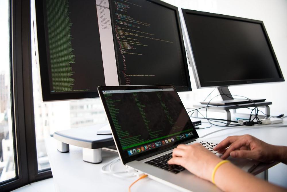 pessoa vendo dados de segurança no notebook e em monitores.