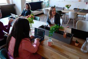 mulheres conversando ao redor de uma mesa sobre tipos de roteadores