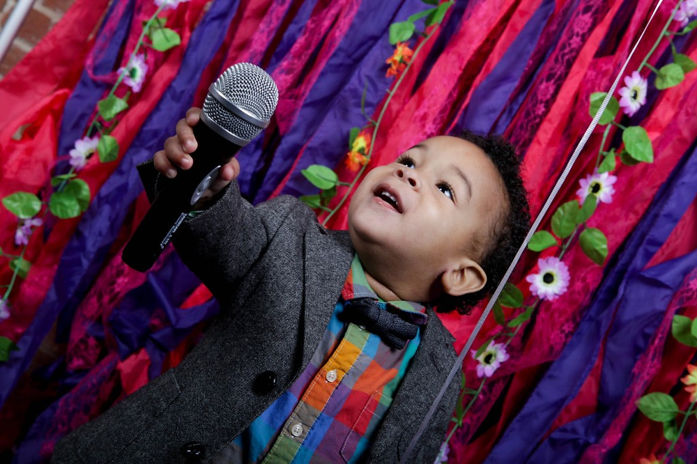 Image of child singing into microphone