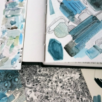 Image of sketchpads on a desk with various blue testing strokes